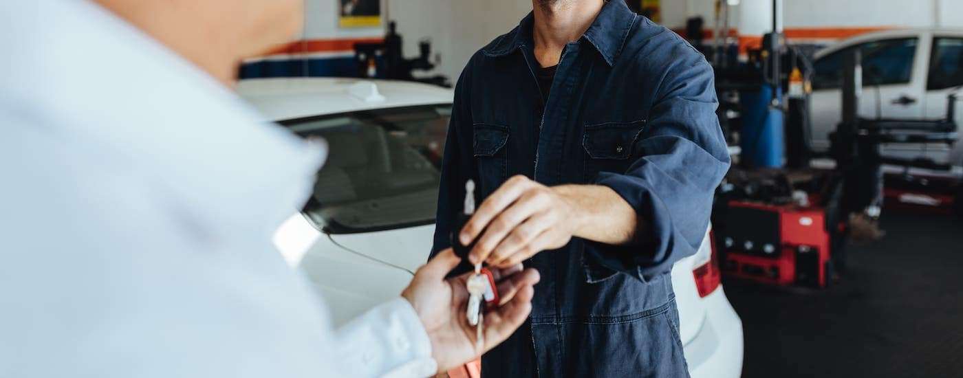 A mechanic handing keys to a customer after servicing Used Cars Louisville