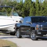 A black 2015 Chevy Silverado 1500, which is popular among used cars in Louisville, is towing a boat past trees.