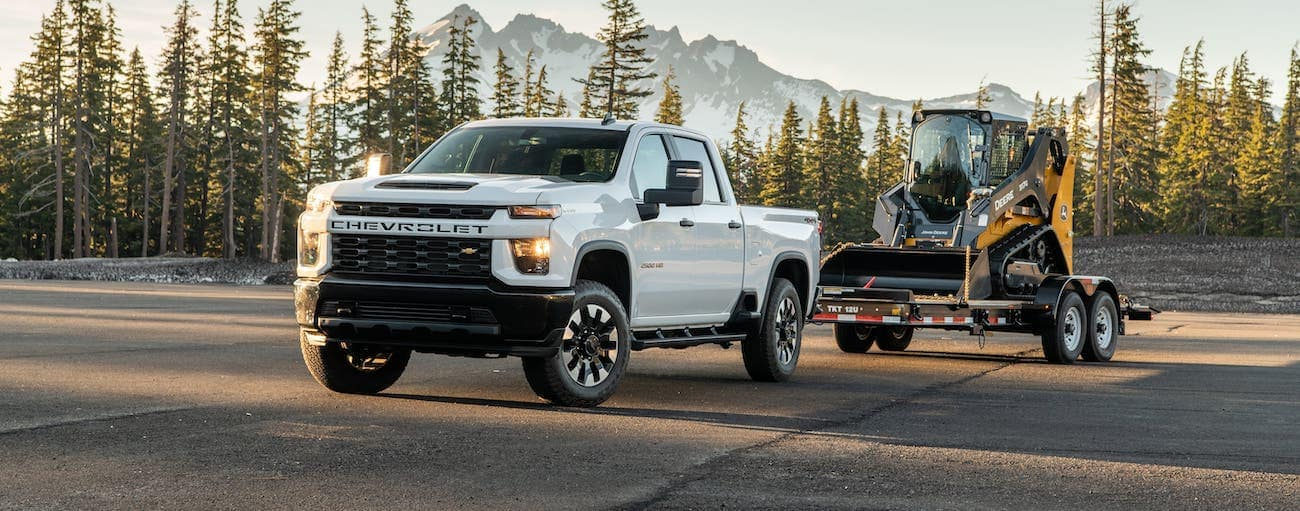 A white 2020 Chevy Silverado 2500HD Custom is towing a small tractor in front of mountains.