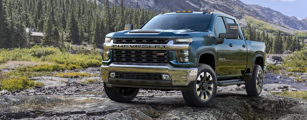 A blue 2020 Chevy Silverado 2500HD LT is parked on a rock in front of a mountain.