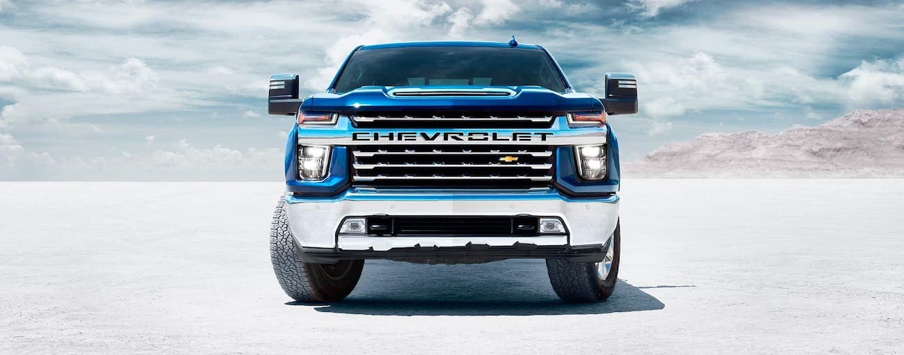 A blue 2020 Chevy Silverado 2500HD LTZ is shown from the front, parked in a salt flat.
