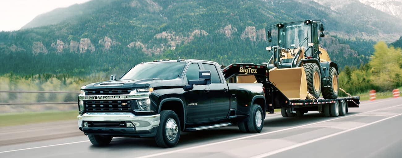 A black 2020 Chevy Silverado 3500HD DRW LT is towing construction equipment.
