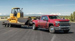 A red 2020 Chevy Silverado 3500HD LTZ is towing construction equipment.
