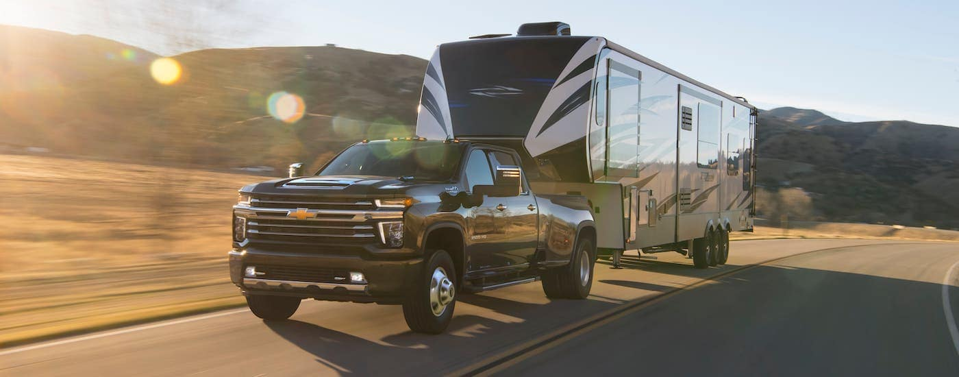 A black 2020 Chevy Silverado 3500HD High Country is towing a camper on a hilly road.