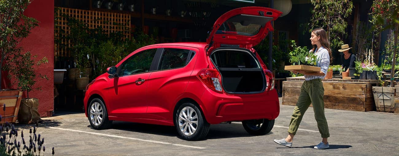 A woman is loading the trunk of her red 2020 Chevy Spark 1LT.