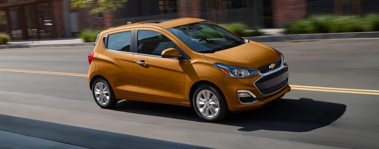 An orange 2020 Chevy Spark is driving past brick buildings.