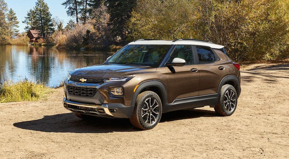 A brown 2021 Chevy Trailblazer, a new SUV among Chevy models, is parked at a pond.