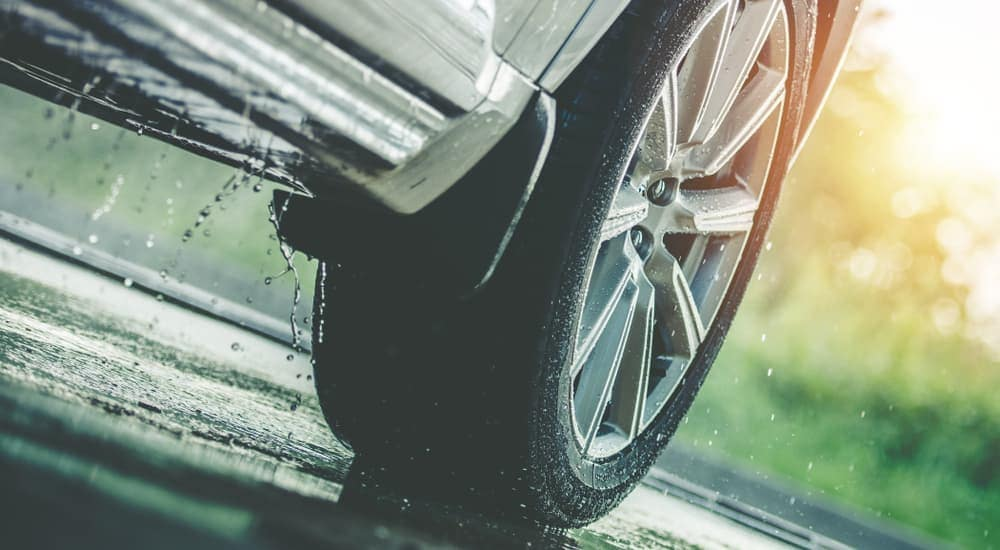 A close up of a tire on a silver car in the rain is shown.