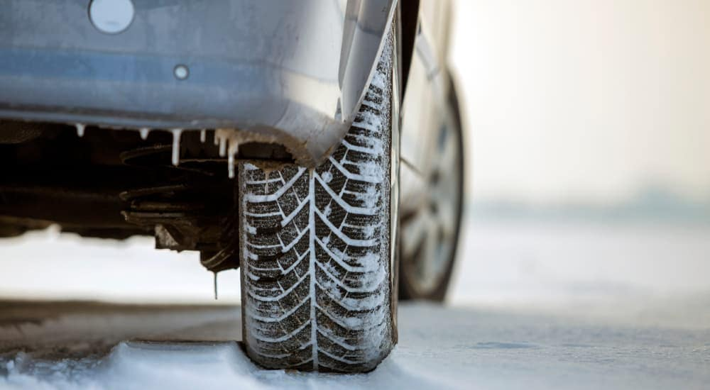 A close up of a silver car's tire in the snow is shown.