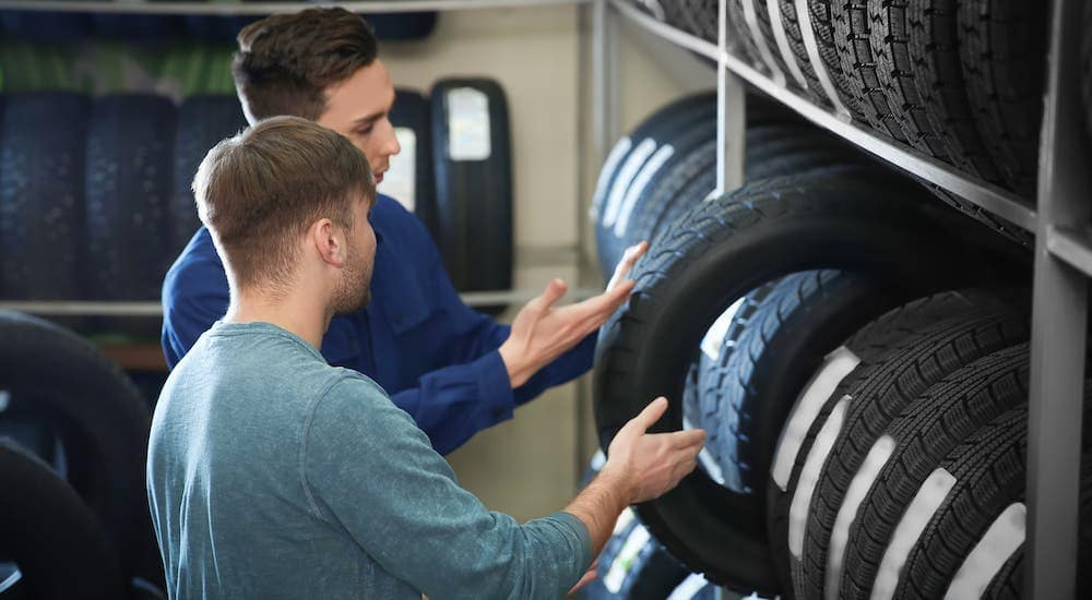 A mechanic at a Cincinnati tire shop is showing a man different types of tires.
