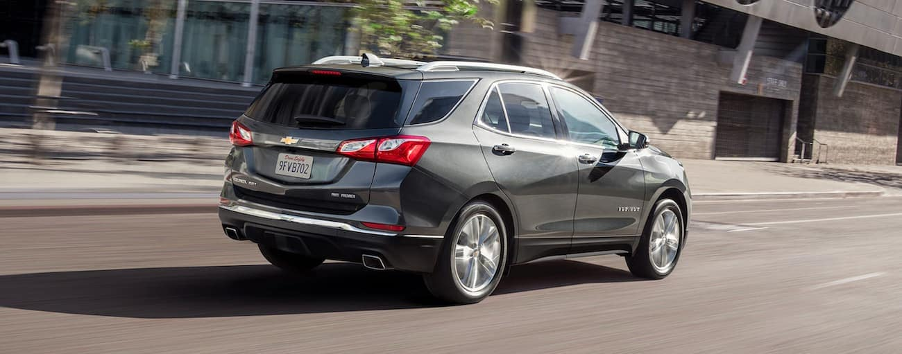 A grey 2020 Chevy Equinox, which wins when comparing the 2020 Chevy Equinox vs 2020 Ford Escape, is driving away on a Cincinnati, OH, street.