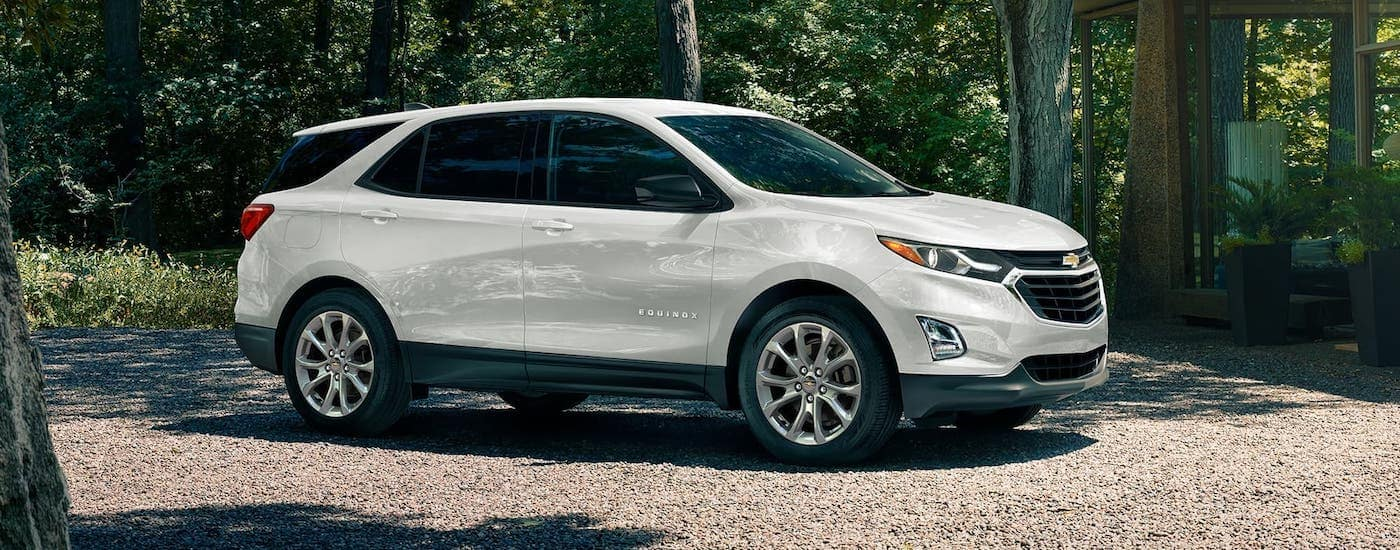 A white 2020 Chevy Equinox is parked in front of a woodland home near Cincinnati, OH.