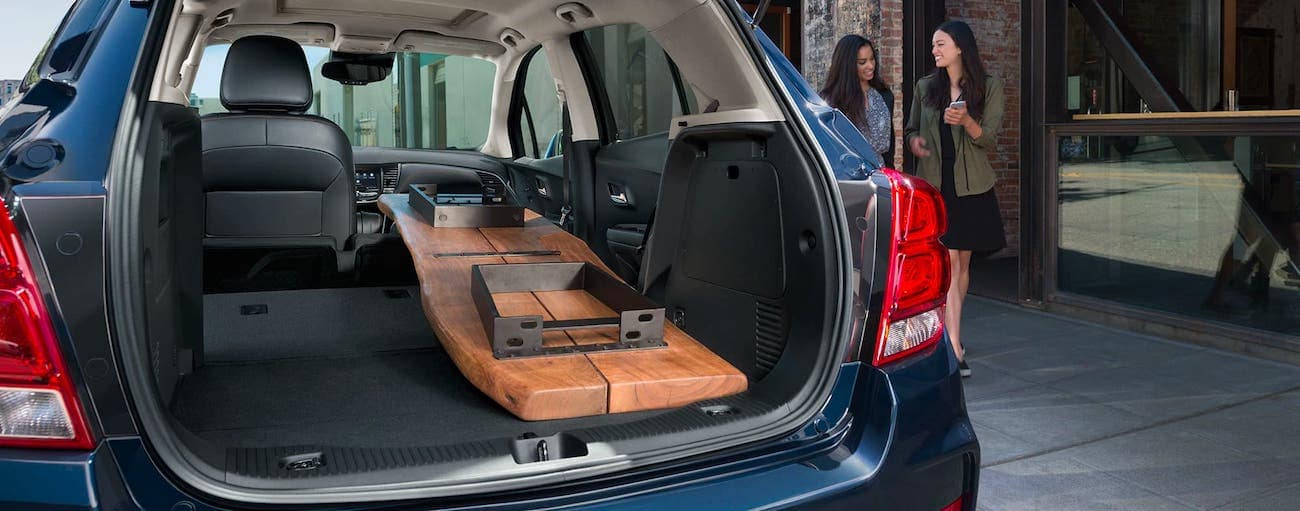 A wooden table is shown sitting in the cargo area of a blue 2020 Chevy Trax which is parked on a Cincinnati, OH, road.