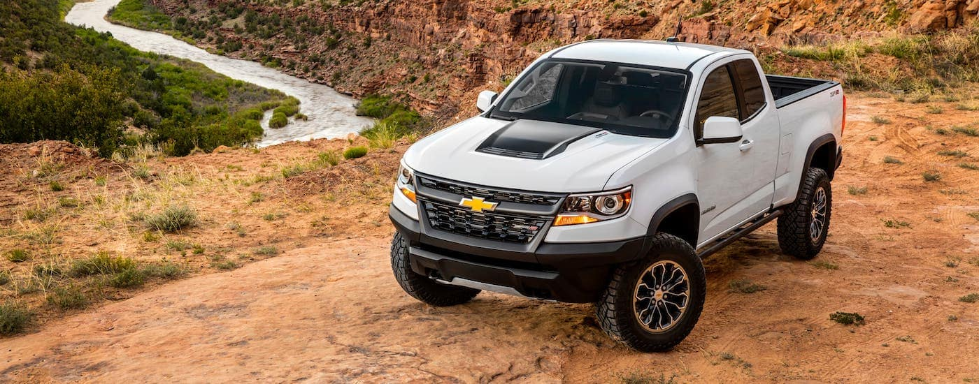 A white 2020 Chevy Colorado ZR2 is parked on a desert cliff overlooking a river.