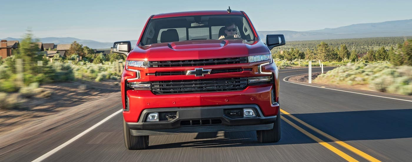 A red 2020 Chevy Silverado 1500 is shown from the front, driving on a desert highway to get Chevy truck parts.