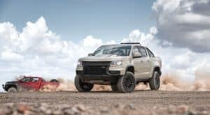 A tan 2021 Chevy Colorado ZR2 is parked on dirt with a red Bison edition of the Chevy truck racing behind it.