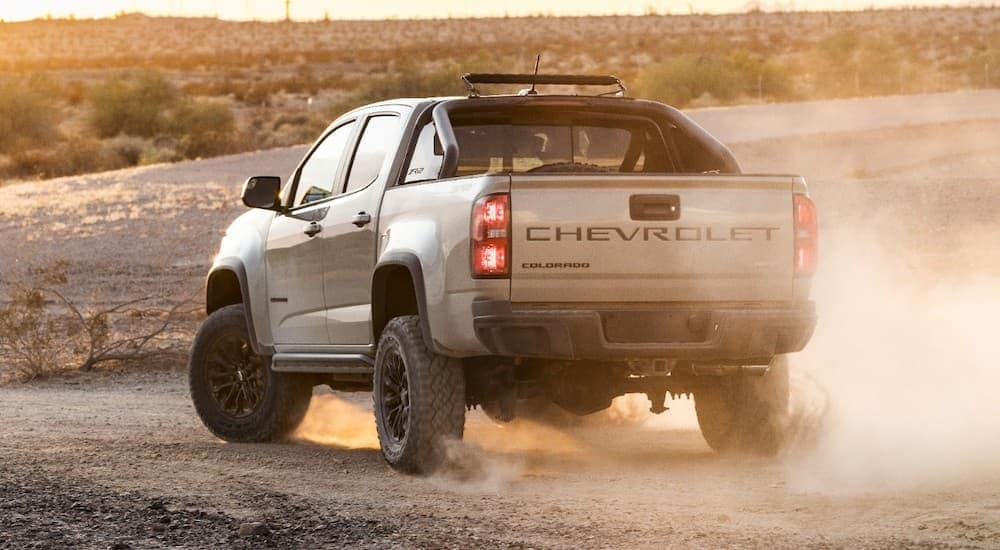 A tan 2021 Chevy Colorado ZR2 is shown from the rear parked in the dirt at sunset.