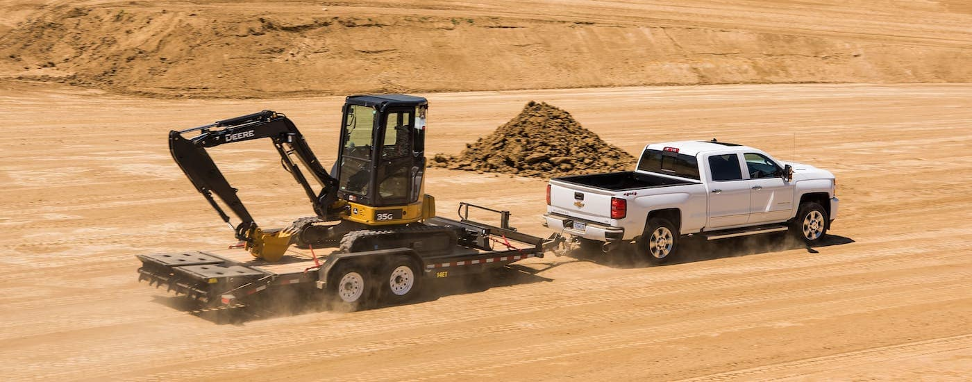 A white 2017 Chevy Silverado 2500HD is towing construction equipment in a dirt field.