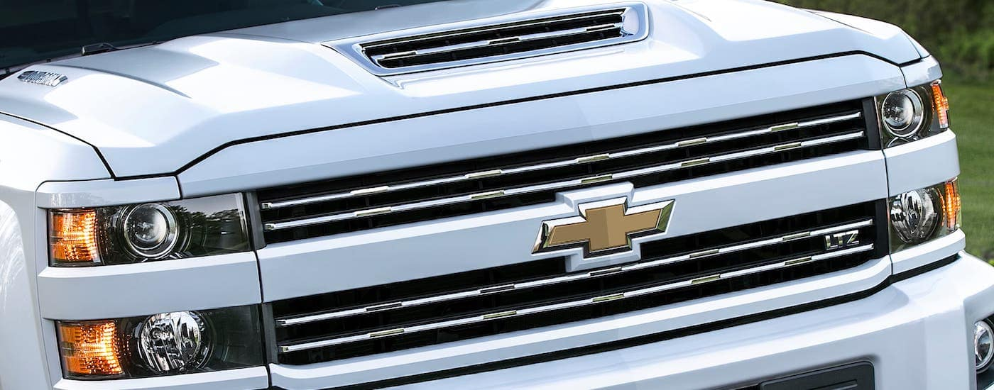 A closeup is shown of the grill on a white 2017 Chevy Silverado 3500HD, a common commercial truck for sale in Cincinnati.