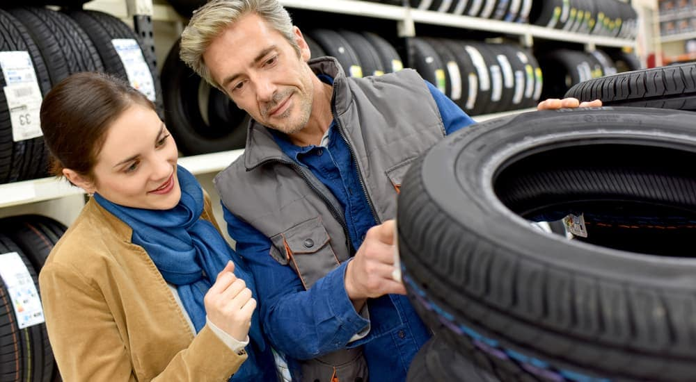 A salesman is helping a woman pick out a tire at a tire shop in Cincinnati, OH.