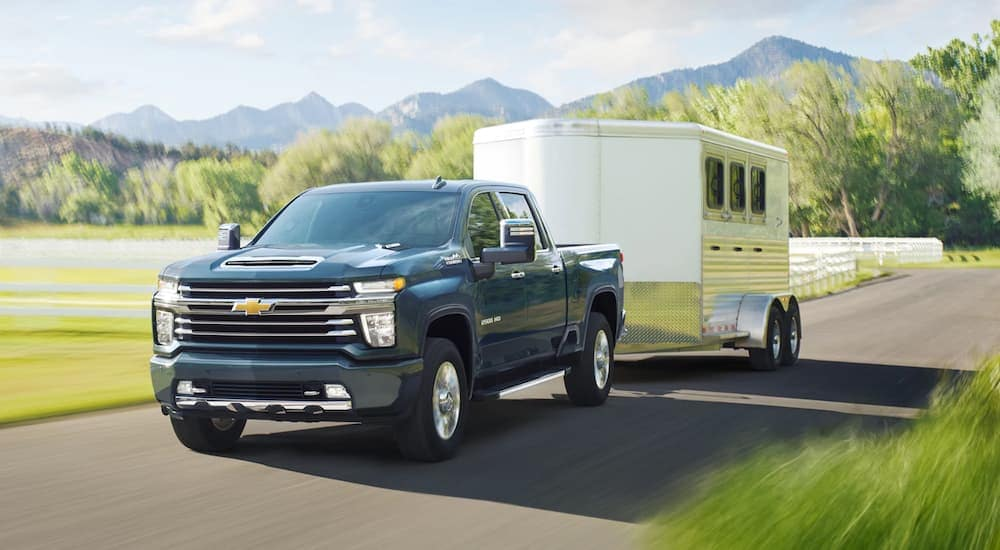 A dark blue 2020 Chevy Silverado 2500HD is towing a horse trailer past a farm with mountains in the distance.