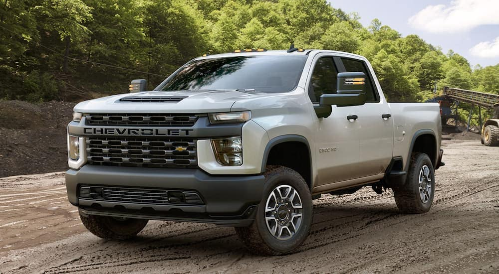 A white 2020 Chevy Silverado 2500HD, which is popular among trucks for sale in Cincinnati, OH, is parked at a construction site.