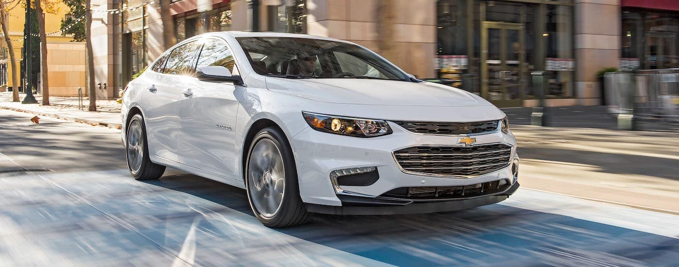 Using the used car finder service you could find a white 2018 Chevy Malibu like this, shown driving through a Cincinnati intersection.