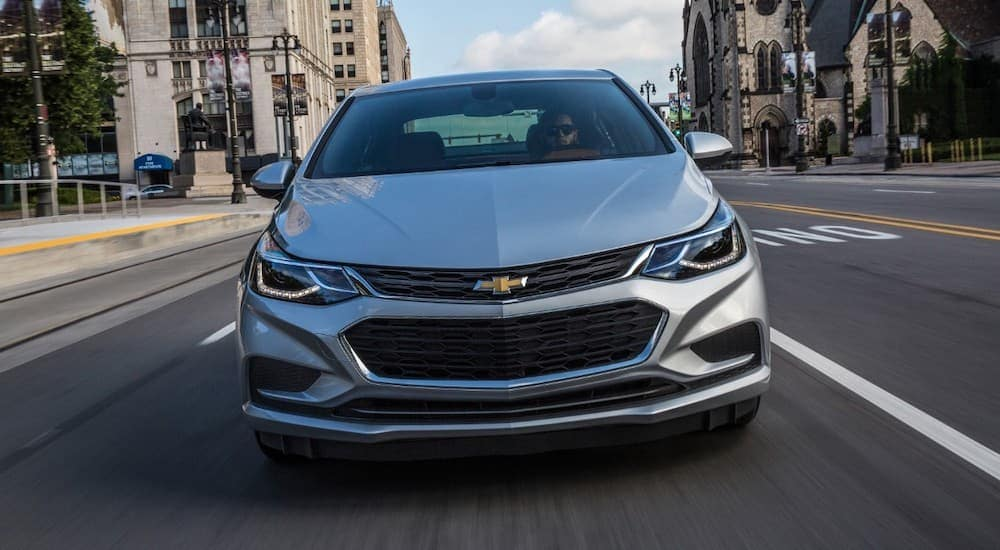 A silver 2017 Chevy Cruze, which is popular among used cars for sale in Ohio, is driving on a city street.