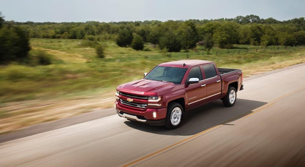 A red 2017 Chevy Silverado is driving past trees and grass on a highway.