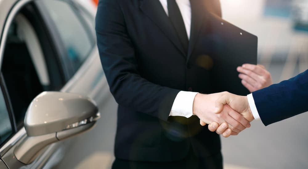 A salesman is shaking hands with a buyer at a Cincinnati, OH, dealership.