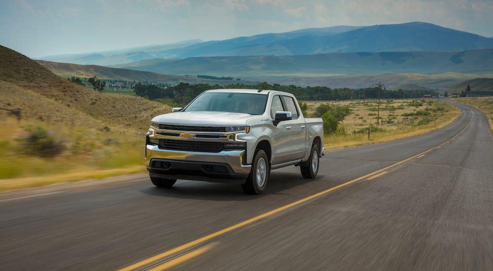A silver 2020 Chevy Silverado without Silverado mud flaps is driving on a highway.