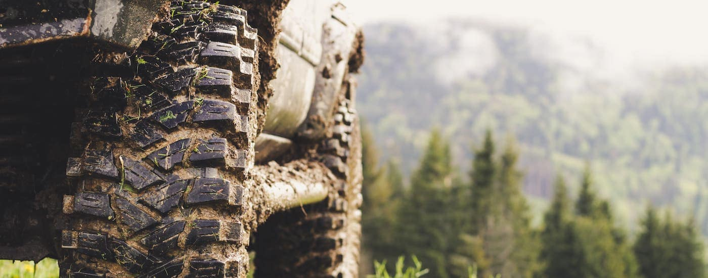 A closeup of a truck's tires is shown covered in mud on a woodland trail.