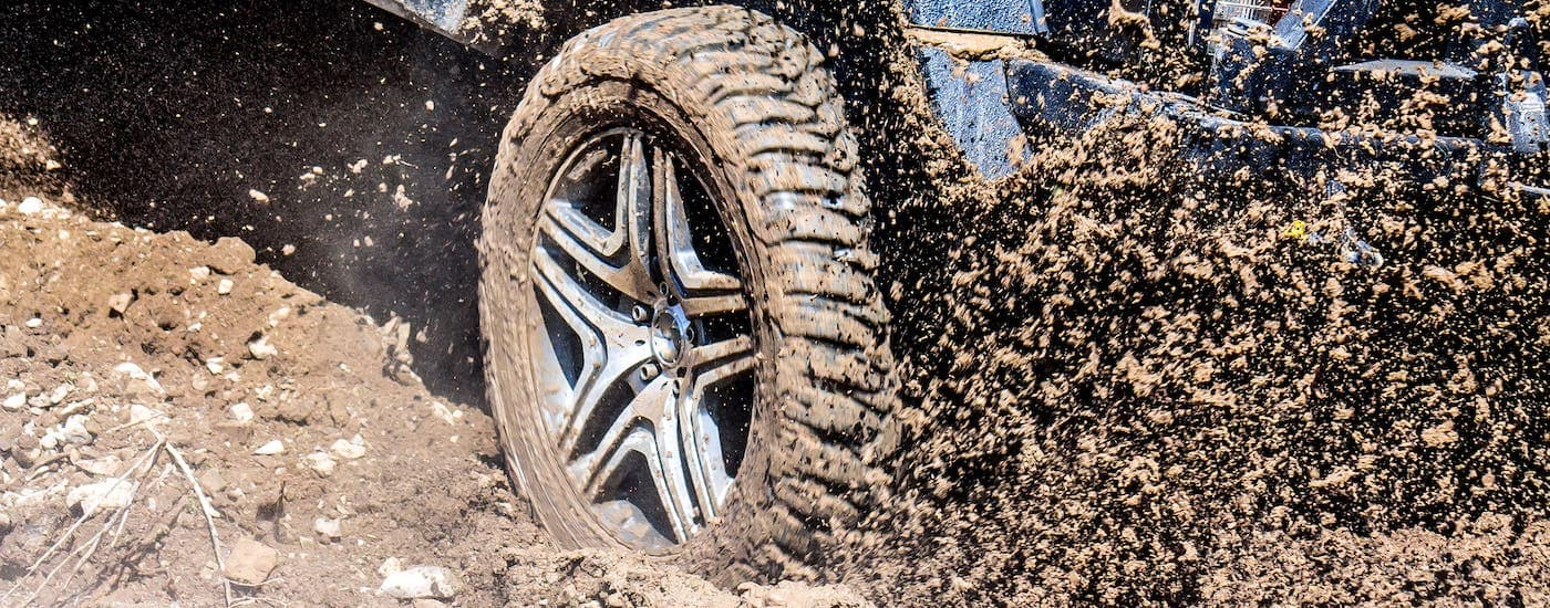 A closeup shows mud being kicked up under a blue truck near Cincinnati, OH.