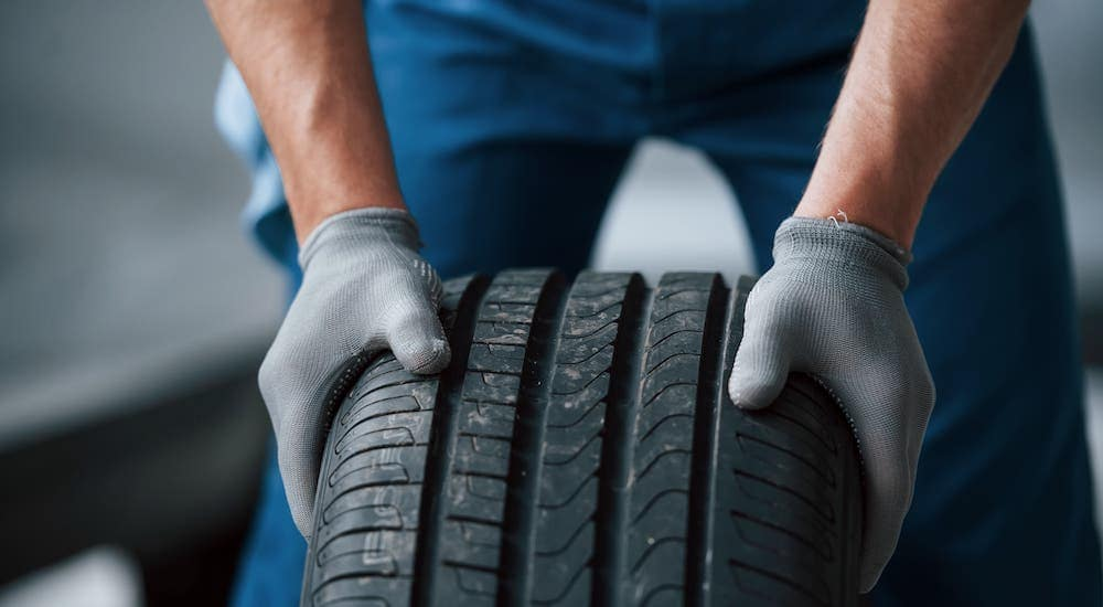 A closeup is shown of a gloved mechanic holding a discount tire in Cincinnati.