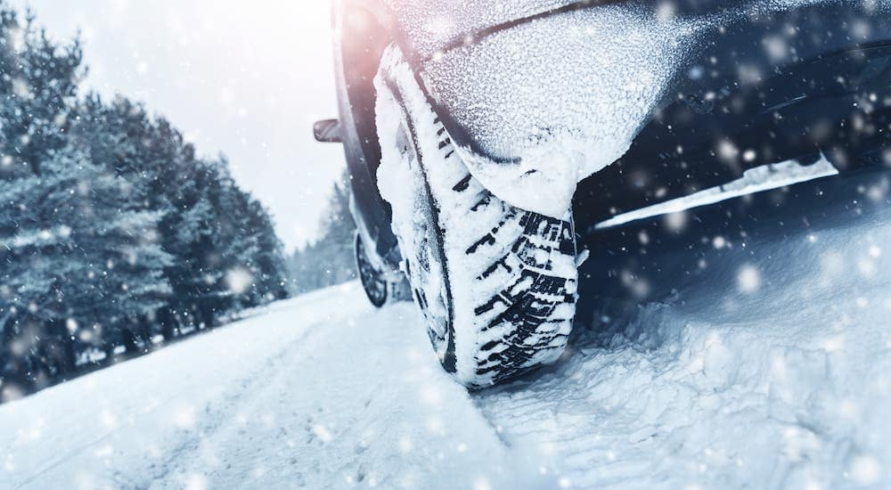 A closeup is shown of a snowy tire on a snow-covered road.