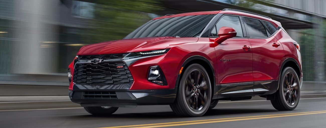 A red 2020 Chevy Blazer RS is driving down a Cincinnati street for a comparison between the 2020 Chevy Blazer vs 2020 Chevy Equinox.