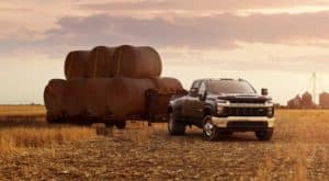 A black 2020 Chevy Silverado 3500HD is parked in a field with a trailer full of hay bales.
