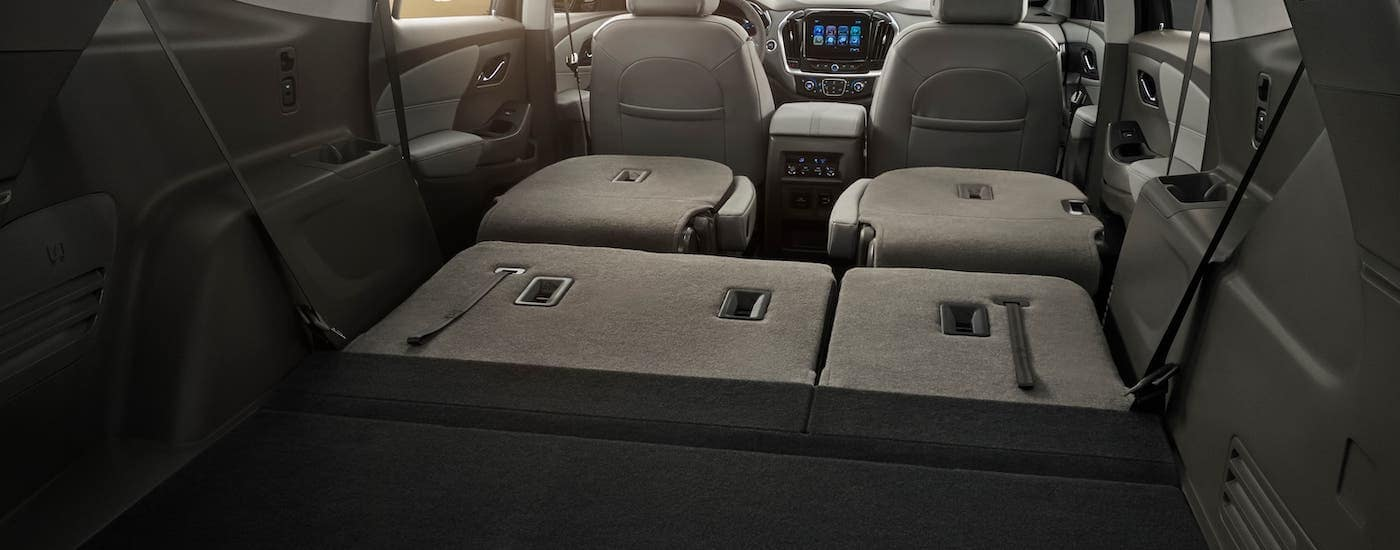 The cargo area is shown in a 2020 Chevy Traverse with the seats folded down.