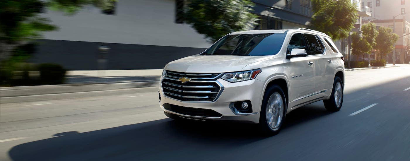 A white 2020 Chevy Traverse is driving on a city street in Cincinnati, OH, after winning the 2020 Chevy Traverse vs 2020 Ford Explorer comparison.