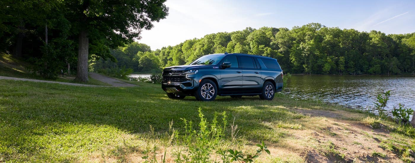 A new Chevy SUV, a black 2021 Chevy Suburban Z71, is parked next to a pond.