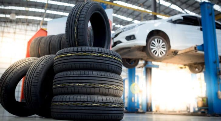 A stack of discount tires in a Cincinnati tire shop are in front of a white car on a lift.
