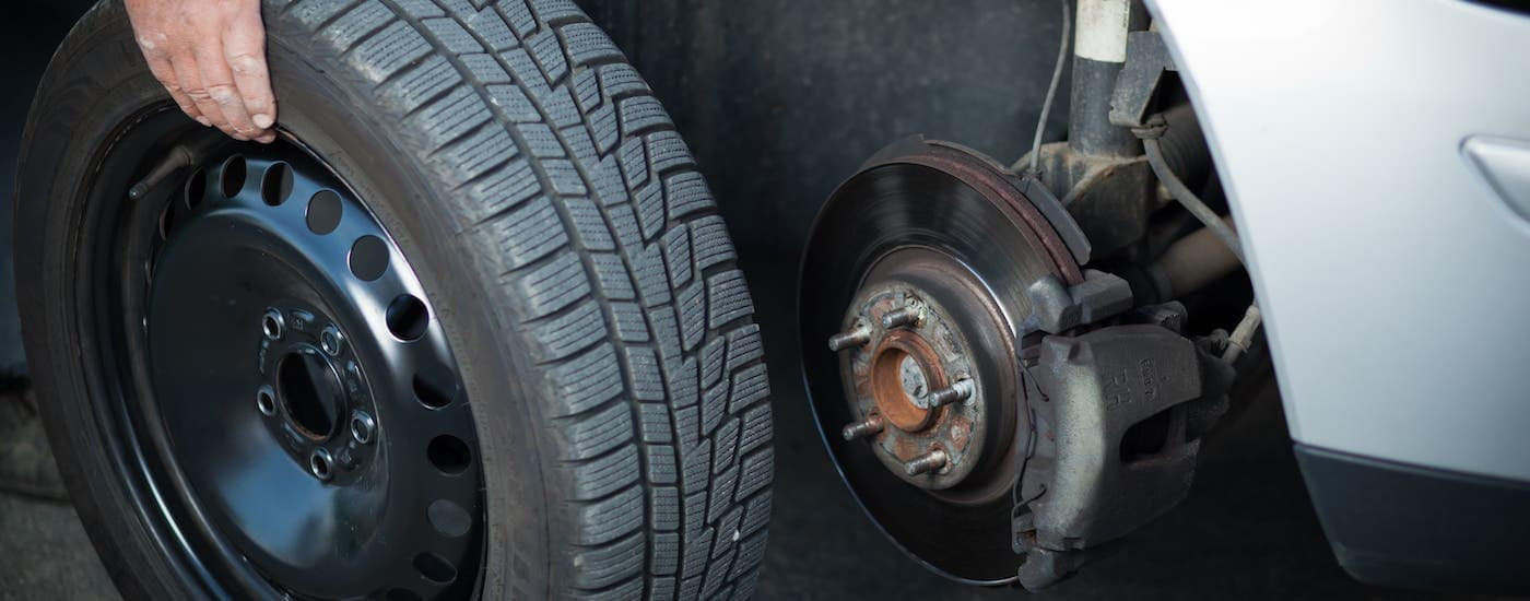 A closeup shows a tire being taken off a car.