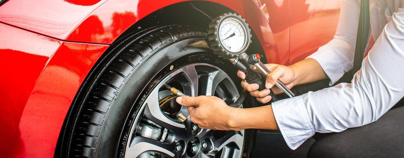 A car owner is checking the tire pressure on a red car.