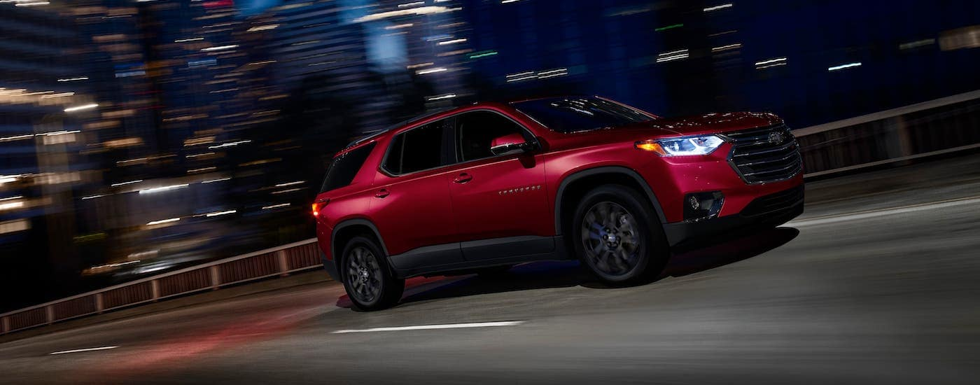 A red 2019 Chevy Traverse RS is driving in a city at night.