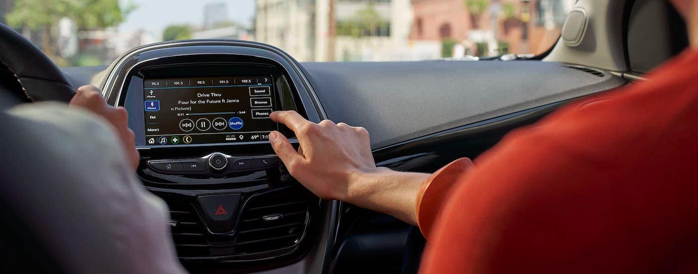 A hand is using the infotainment screen in a 2021 Chevy Spark.