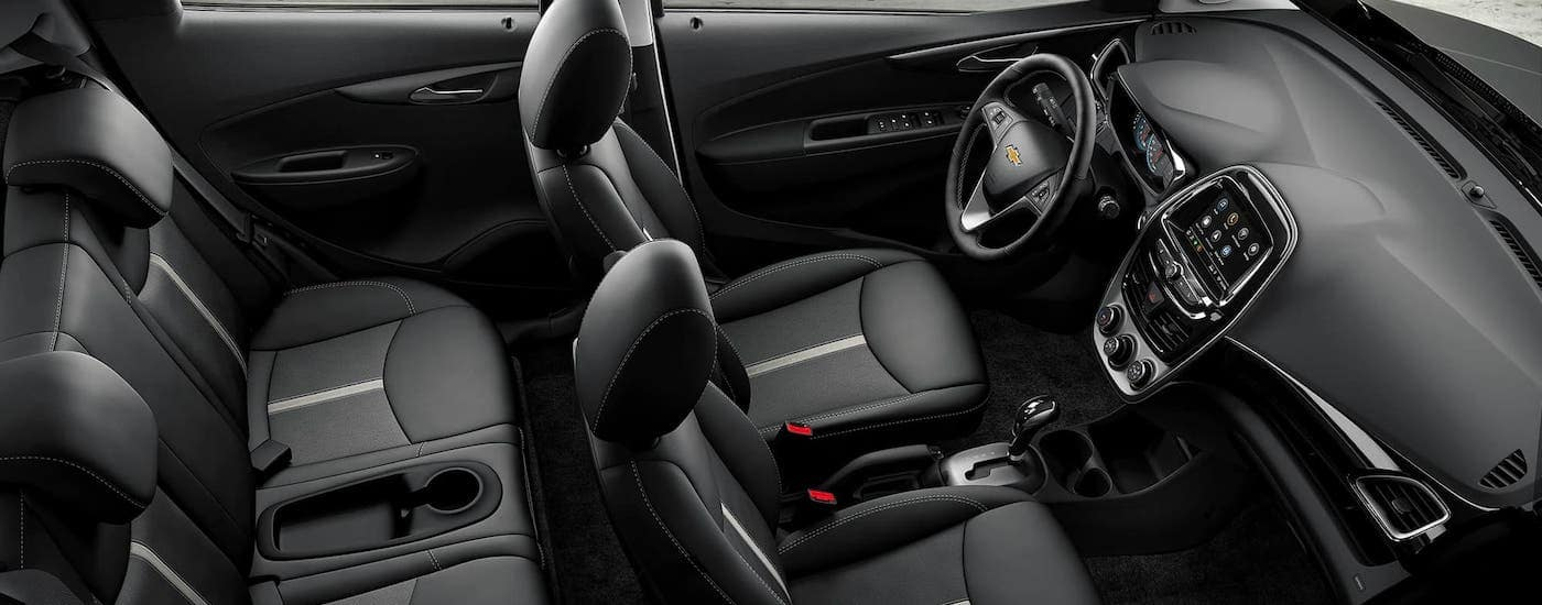 The black interior of a 2021 Chevy Spark is shown from the side and a high angle.
