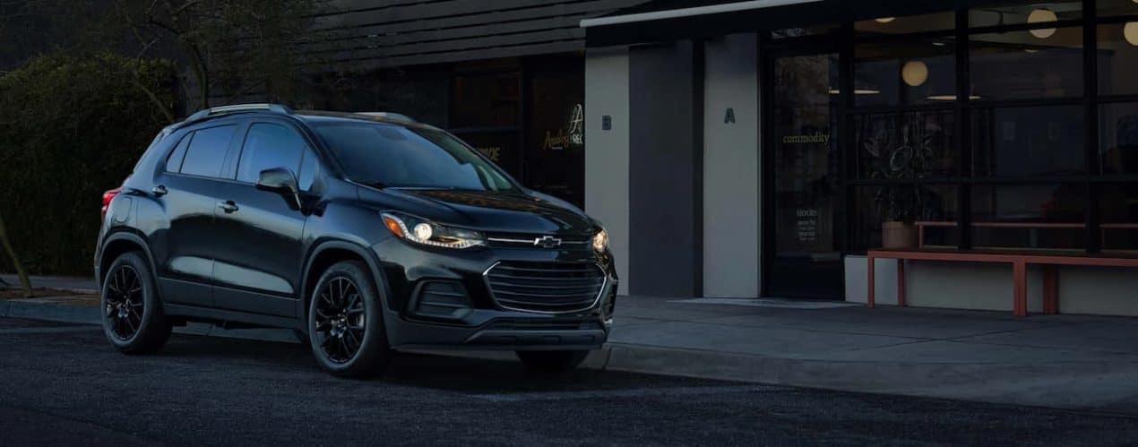 A black 2021 Chevy Trax Midnight Edition is on a city street near Cincinnati, OH.