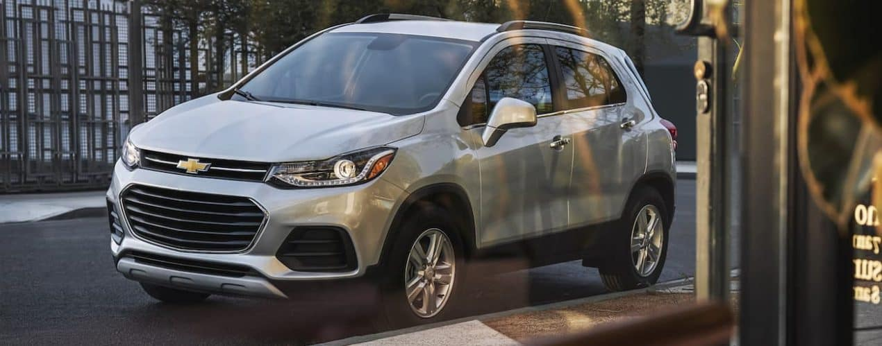 A silver 2021 Chevy Trax is shown through a window on a city street.