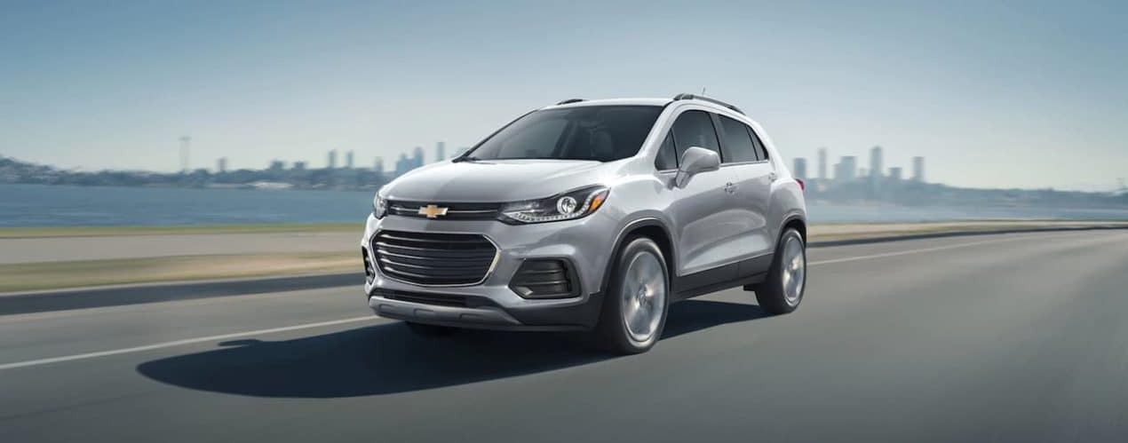 A white 2021 Chevy Trax is driving on a highway with a city skyline behind it.