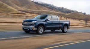 A dark blue 2021 Chevy Silverado 1500 is driving past hills outside Cincinnati, OH.